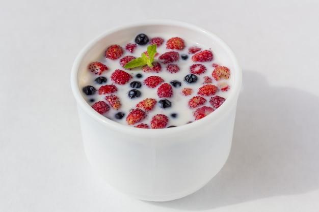 Fragole fresche con latte in una tazza bianca. Foto Premium