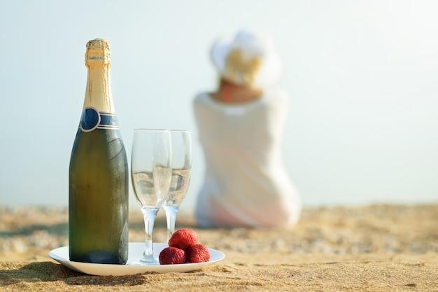 Fragole fresche di bacche, bottiglia di champagne, bicchieri e la donna sulla spiaggia. Foto Premium