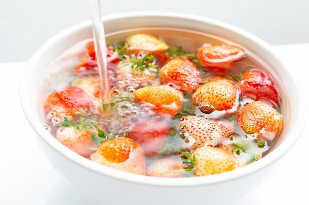 Fragole imbevute di acqua lavare la frutta fresca su bianco. Foto Premium