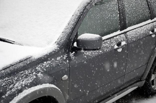 Frammento dell'auto sotto uno strato di neve dopo una fitta nevicata. il corpo dell'auto è coperto di neve bianca Foto Premium