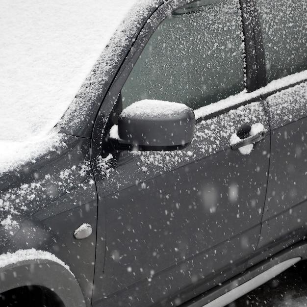 Frammento dell'auto sotto uno strato di neve dopo una fitta nevicata Foto Premium