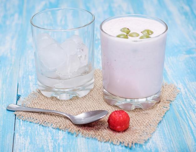 Frappè con fragole, uva spina e ghiaccio su un tavolo blu. Foto Premium