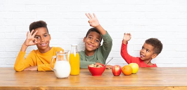Fratelli afroamericani facendo colazione e facendo segno ok Foto Premium