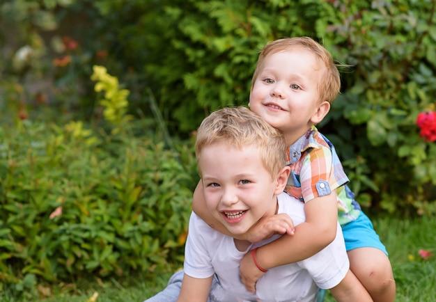 Fratelli felici che abbracciano nel giardino Foto Premium