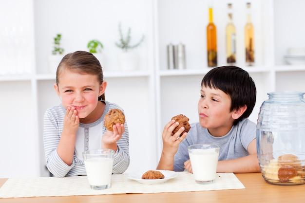 Fratelli felici che mangiano biscotti e bevendo latte Foto Premium