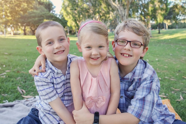 Fratelli felici e sorella che giocano al parco Foto Premium