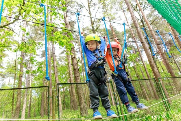 Fratelli gemelli nel casco cammina con la corda Foto Premium