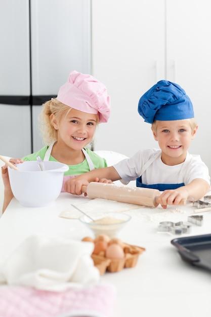Fratelli germani svegli che cuociono insieme i biscotti nel kicthen Foto Premium