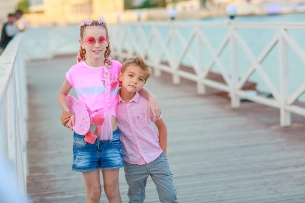Fratello e sorella camminano insieme e si divertono per strada senza persone Foto Premium
