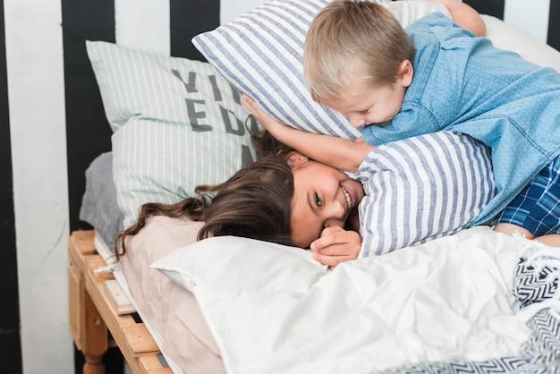 Fratello e sorella che giocano con i cuscini sul letto Foto Gratuite
