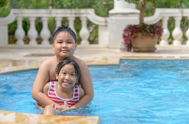 Fratello e sorella giocano in piscina, Foto Premium