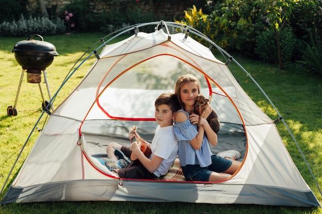 Fratello piccolo e sorella che godono del picnic mentre sedendosi in tenda Foto Gratuite