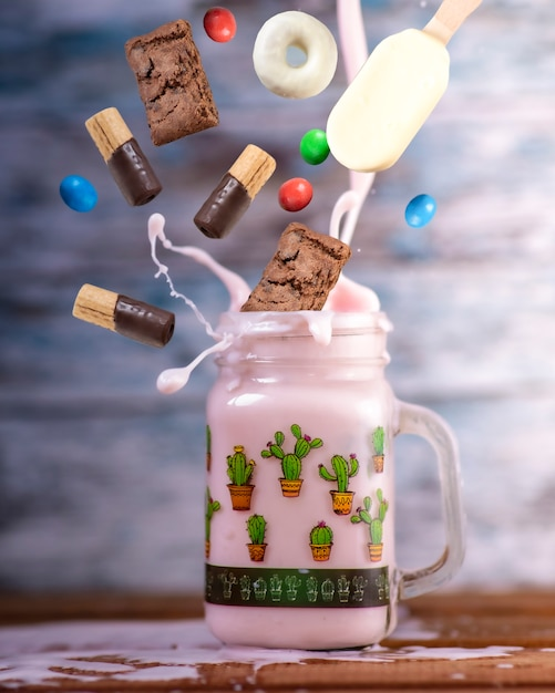 Freakshake alla fragola rosa con dolci nell'aria che cade Foto Premium