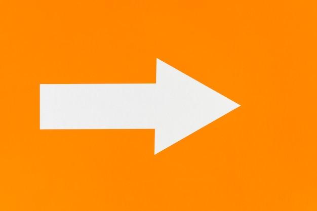 Freccia bianca su sfondo arancione minimalista Foto Gratuite