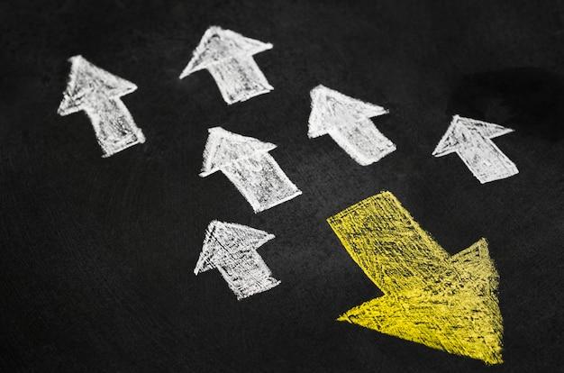 Freccia gialla nel gruppo di frecce bianche con direzione diversa Foto Gratuite