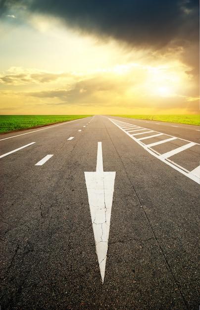 Freccia su asfalto stradale al tramonto Foto Premium