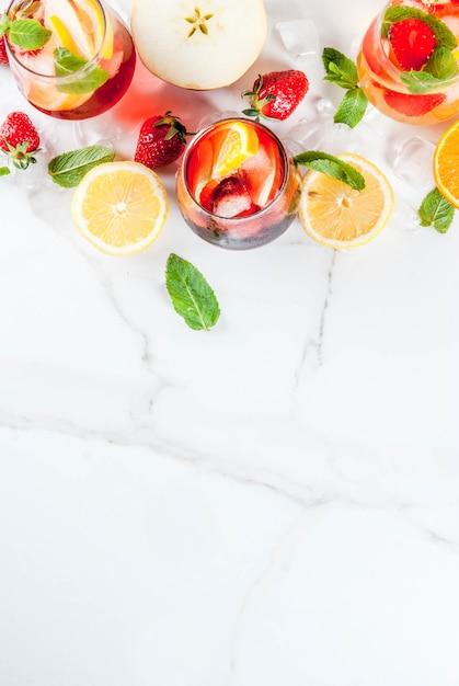 Freddo bianco rosa e rosso cocktail sangria con frutti di bosco freschi e menta. Foto Premium
