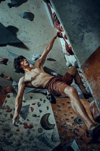 Free climber arrampicata su masso artificiale al chiuso Foto Gratuite