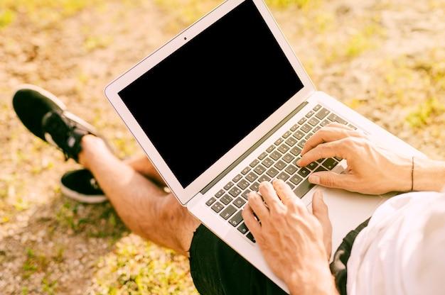 Free lance maschii che per mezzo del computer portatile mentre lavorando fuori Foto Gratuite