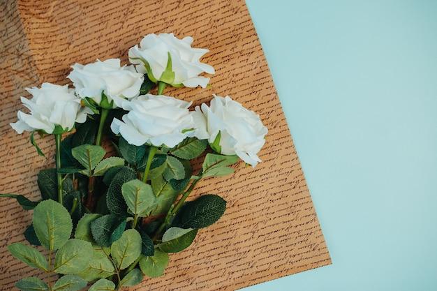Freschezza primaverile rose bianche con foglie verdi. belle rose bianche con gambo lungo sulla carta kraft. Foto Premium