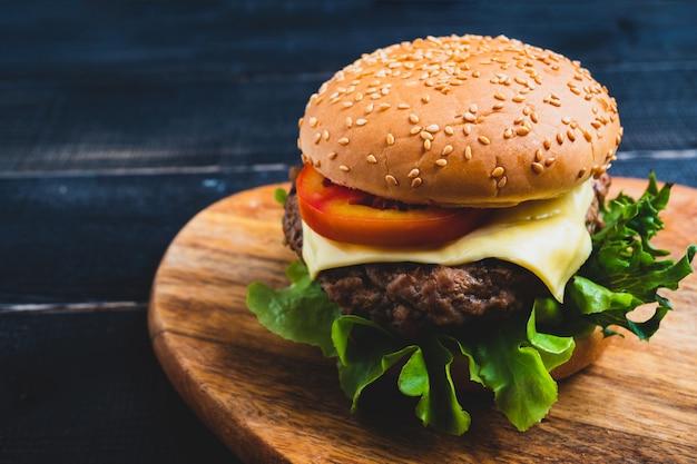 Fresco gustoso hamburger fatti in casa con verdure fresche, lattuga, pomodoro, formaggio su un tagliere. Foto Premium