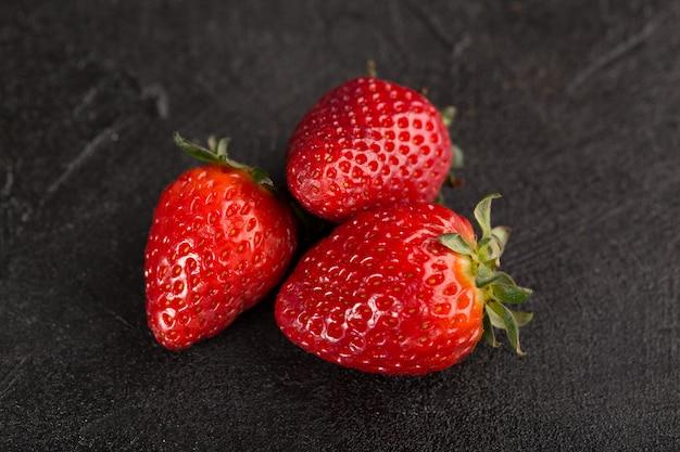 Fresco rosso dolce di tre fragole isolato sul pavimento scuro Foto Gratuite