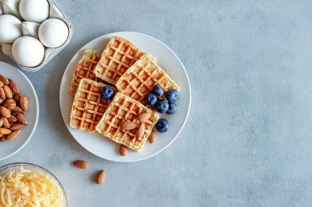 Fringuelli al mirtillo. waffle di uova e formaggio per la colazione. dieta keto. waffle al formaggio. Foto Premium