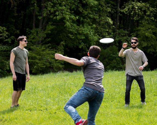 Frisbee di lancio del maschio adulto per l'amico in parco Foto Gratuite