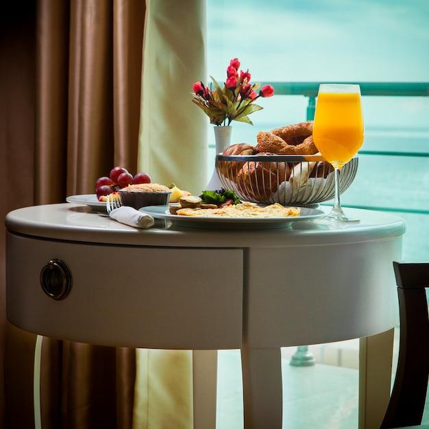 Frittata colazione vista laterale con funghi, succo di frutta, cornetti in servizio in camera con vista sul mare Foto Gratuite