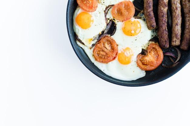Frittata con pomodori in padella su uno sfondo bianco. Foto Premium