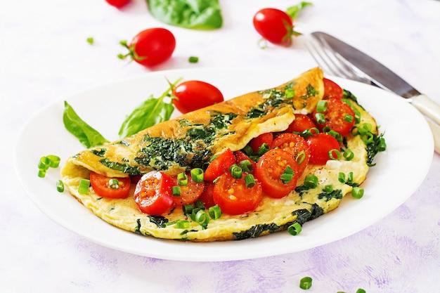 Frittata con pomodori, spinaci e cipolla verde sul piatto bianco. Foto Premium