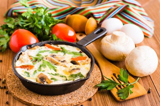 Frittata italiana e ingredienti per la cottura Foto Premium