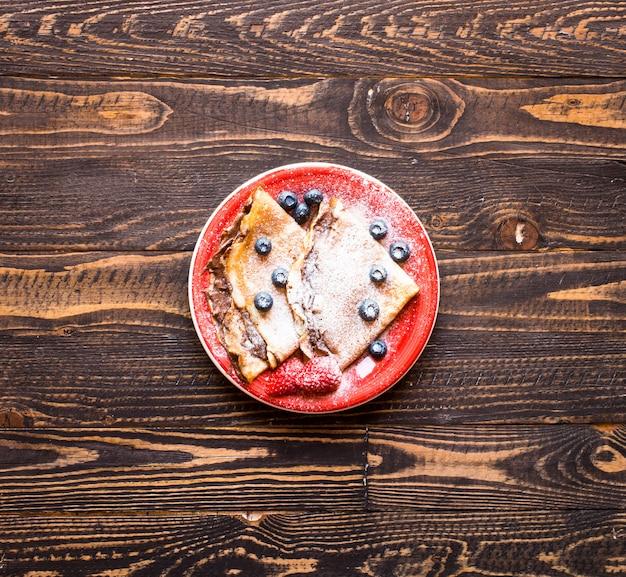Frittelle di fragole fresche o crepes con bacche e cioccolato Foto Premium