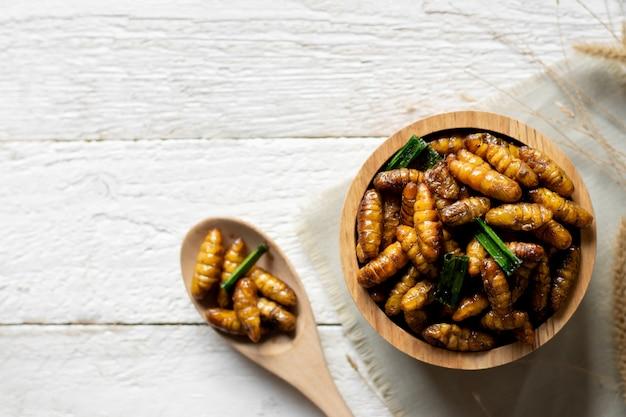 Frittura di insetti in una ciotola posta su un tavolo di legno bianco, cibo proteico sano. Foto Premium