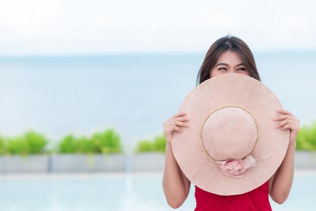 Fronte asiatico sorridente della copertura della donna con il cappello rotondo Foto Premium