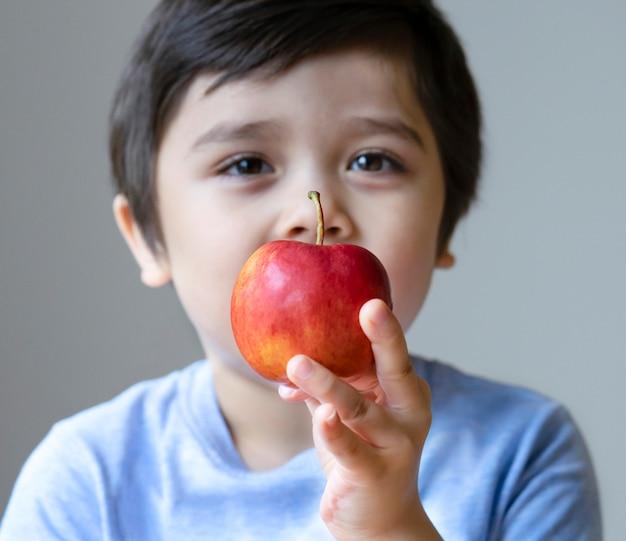 Fronte confusa del ragazzo sveglio che tiene mela rossa organica sulla sua mano e che esamina macchina fotografica Foto Premium