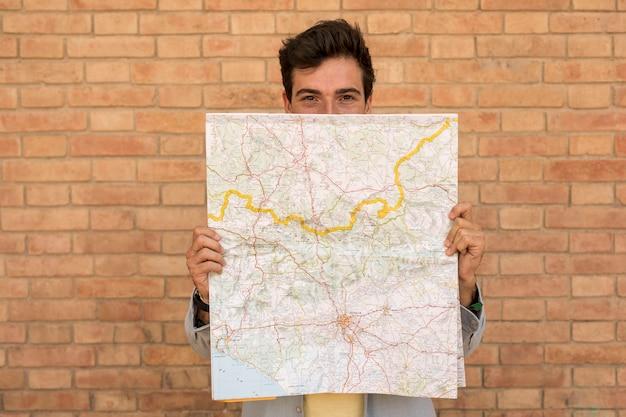Fronte della copertura dell'uomo di vista frontale con una mappa Foto Gratuite