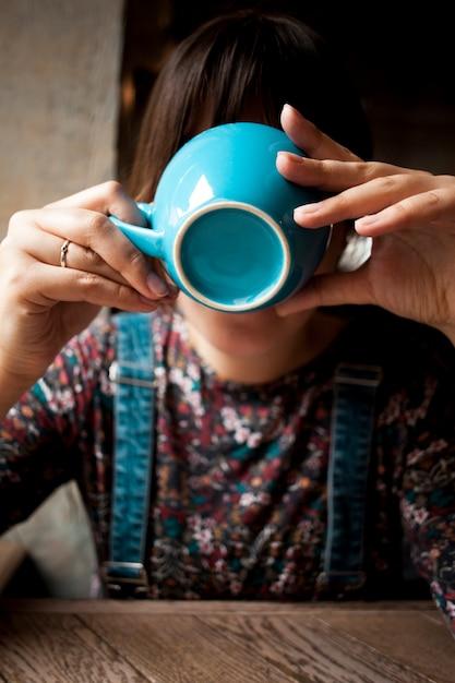 Fronte della copertura della donna con la tazza ceramica blu mentre bevendo caffè Foto Gratuite