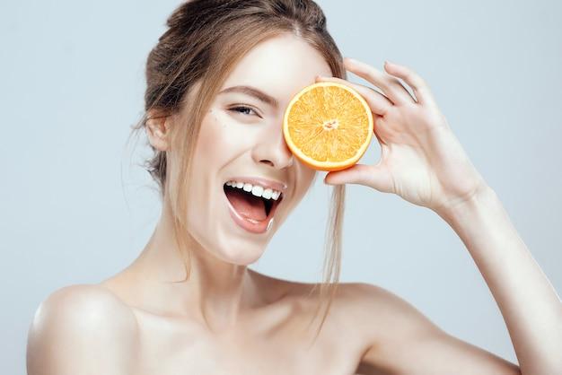 Fronte di bella donna con arancia succosa Foto Premium