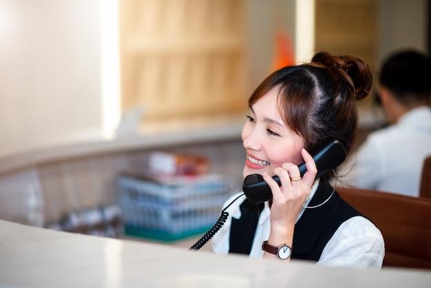 Fronte sorridente della donna asiatica professionale astuta in operatore, dipartimento della call center. telefono che lavora con happy service mind dipartimento di telecomunicazioni Foto Premium