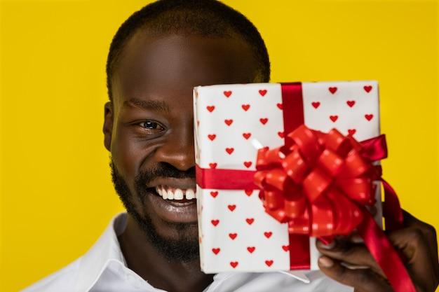 Frontview di ridere giovane ragazzo afroamericano barbuto con un regalo in mano che ha chiuso metà del viso in camicia bianca Foto Gratuite