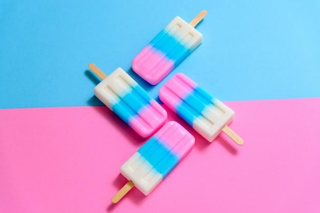Fruit ice cream stick, popsicle, ice pop o freezer pop con copyspace su sfondo blu pastello e texture o rosa Foto Premium