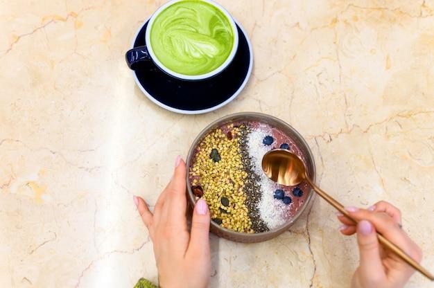 Frullato ciotola di cibo crudo e tazza di tè verde latte matcha e mani femminili con un cucchiaio di metallo, pronto da mangiare, sul tavolo Foto Premium