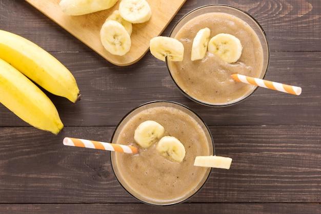 Frullato di banana top shot su fondo di legno Foto Premium
