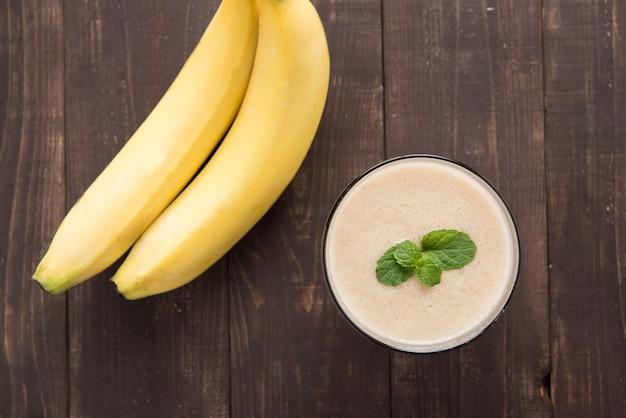 Frullato di banana top shot sul tavolo di legno Foto Premium