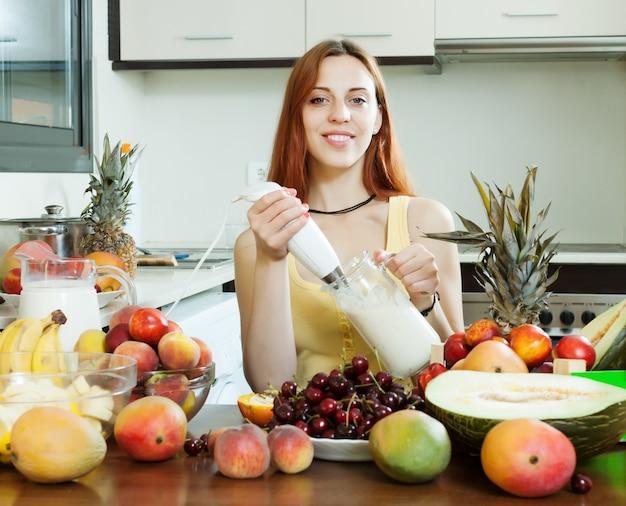 Frullato di cucina tradizionale di donna con frutta Foto Gratuite