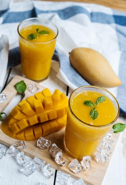 Frullato di mango rinfrescante e sano in un bicchiere con mango Foto Premium