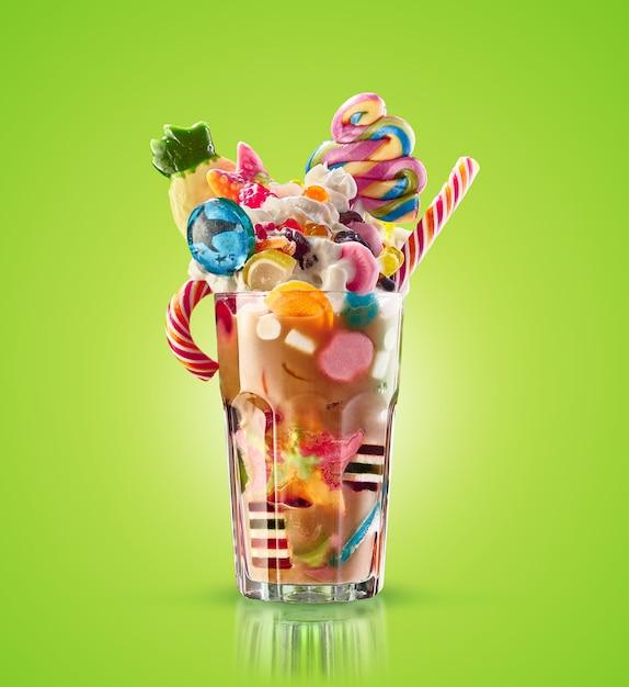 Frullato di mostri, frullato di caramello strano isolato. cocktail colorato e festivo di frappè con i dolci, gelatina. matrice colorata del frappé del caramello di dolci e ossequi differenti del bambino in vetro. frappè dolce Foto Premium