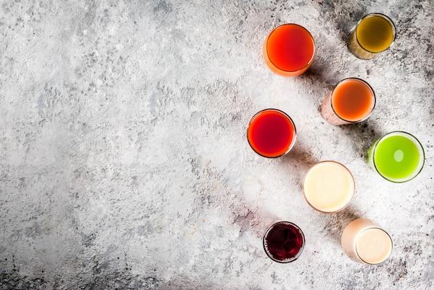 Frullato differente dei succhi dell'alimento sano, della frutta e delle verdure nel copyspace di vista superiore di vetro Foto Premium