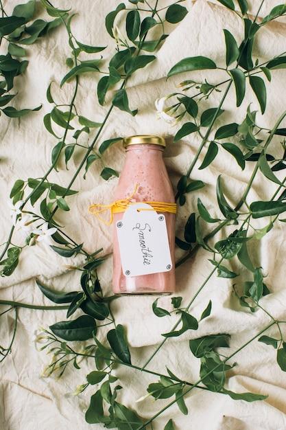 Frullato rosa in una bottiglia accanto alle foglie Foto Gratuite